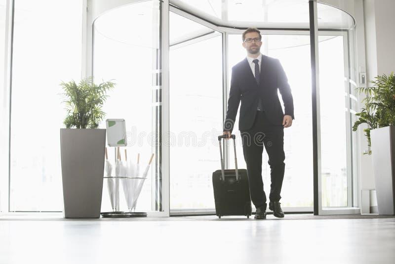 Homem de negócios com centro de convenções entrando da bagagem fotos de stock