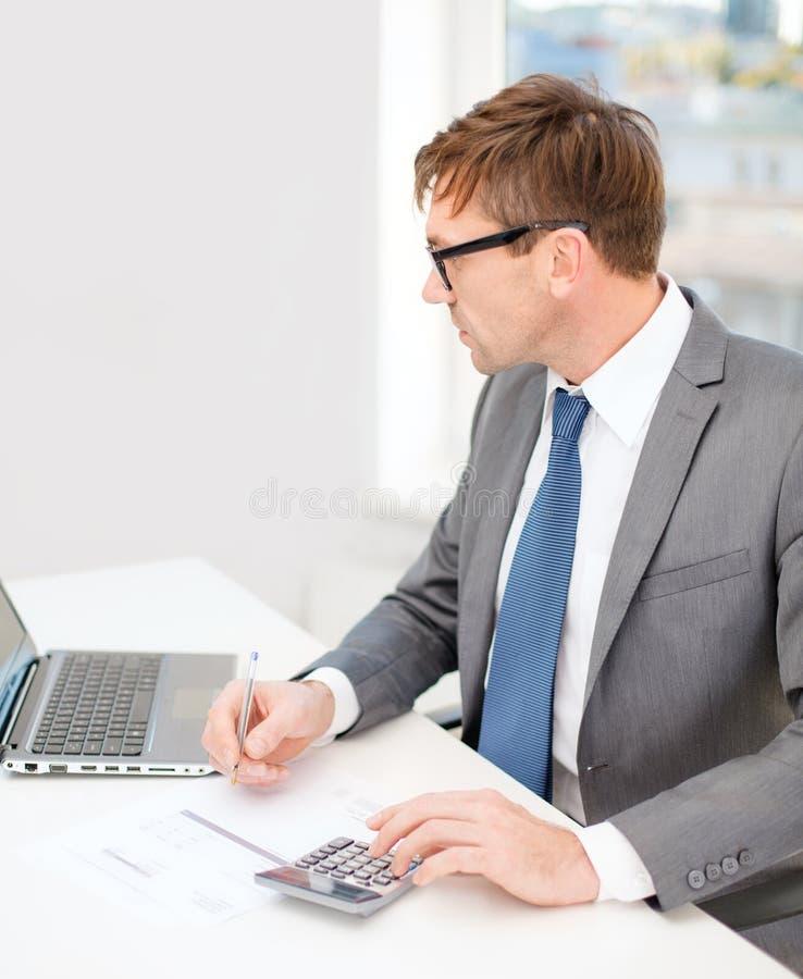 Homem de negócios com computador, papéis e calculadora fotos de stock