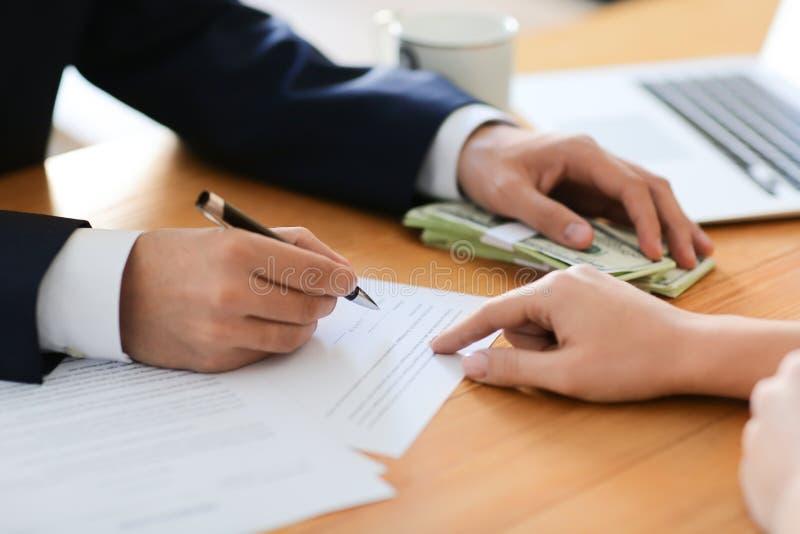 Homem de negócios com contrato de assinatura do subôrno na tabela, close up Conceito da corrup??o fotografia de stock royalty free
