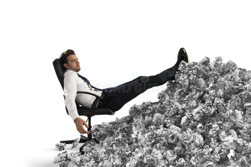 Homem de negócios com folha de papel em qualquer lugar Enterrado pela burocracia conceito do excesso de trabalho imagens de stock royalty free