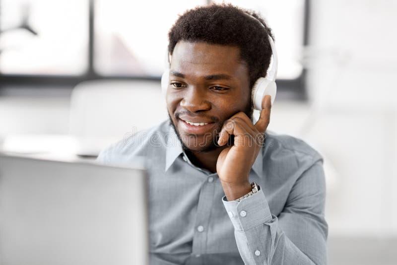 Homem de negócios com fones de ouvido e computador no escritório fotografia de stock royalty free