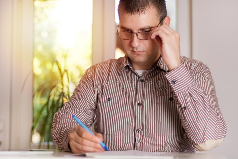 Homem de negócios com funcionamento de vidros no escritório moderno imagem de stock royalty free