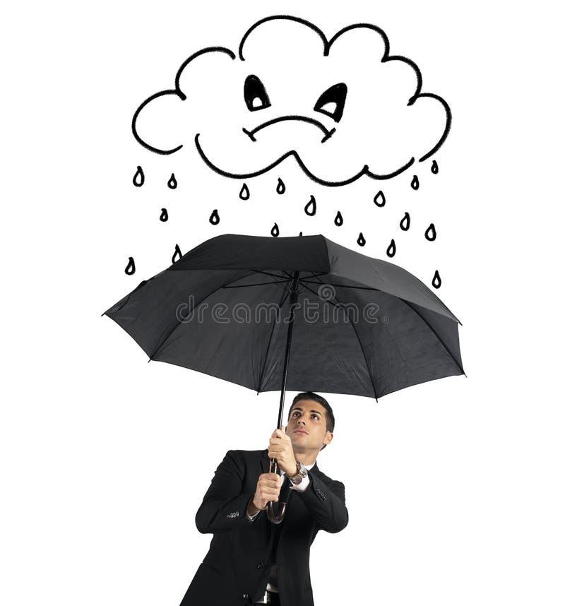 Homem de negócios com guarda-chuva e uma nuvem irritada com chuva Conceito da crise e de problemas financeiros Isolado no branco fotos de stock royalty free