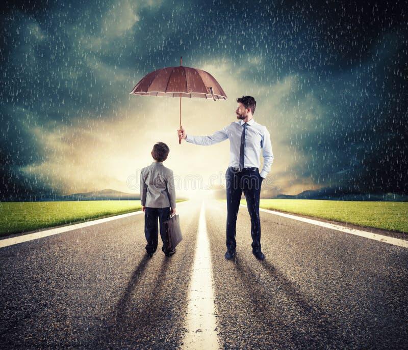 Homem de negócios com guarda-chuva que protege uma criança Conceito da proteção nova da economia e da partida foto de stock