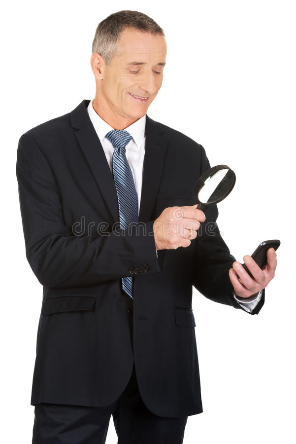 Homem de negócios com lupa e telefone celular fotografia de stock royalty free