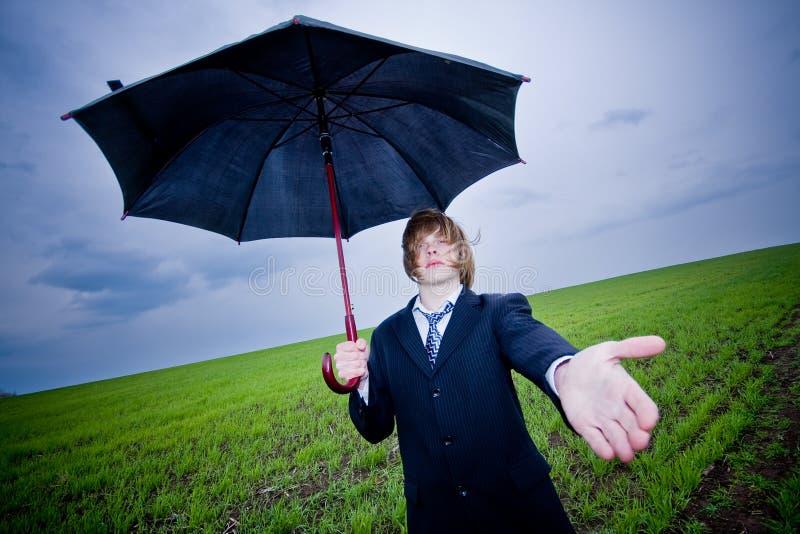 Homem de negócios com mão outstretching do guarda-chuva fotos de stock royalty free