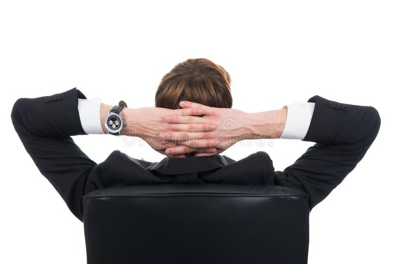 Homem de negócios com mãos atrás da cabeça que relaxa na cadeira fotografia de stock royalty free