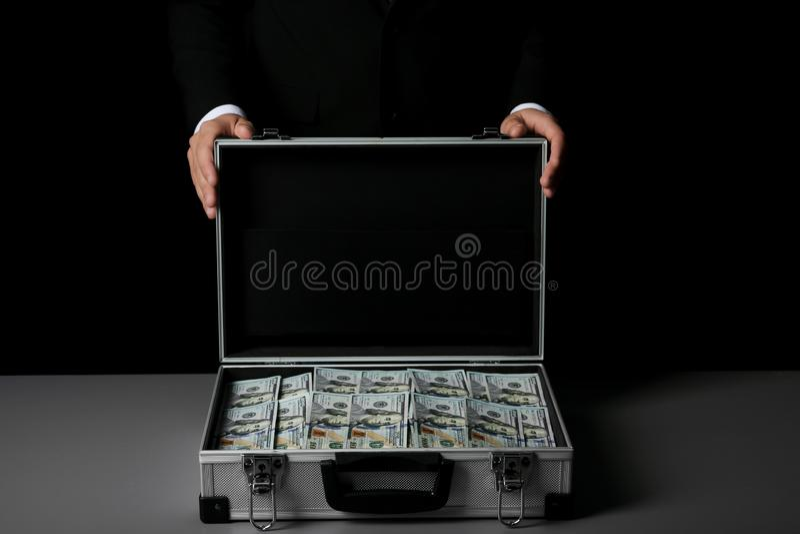 Homem de negócios com a mala de viagem completa do dinheiro fotos de stock