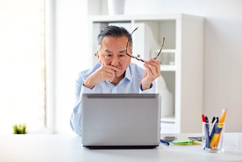 Homem de negócios com monóculos e portátil no escritório fotos de stock