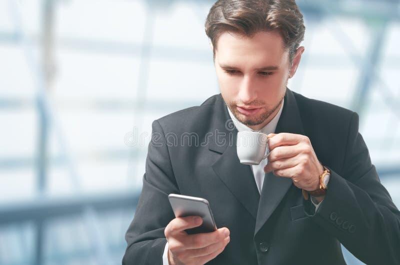 Homem de negócios com o copo do telefone celular e de café imagem de stock royalty free