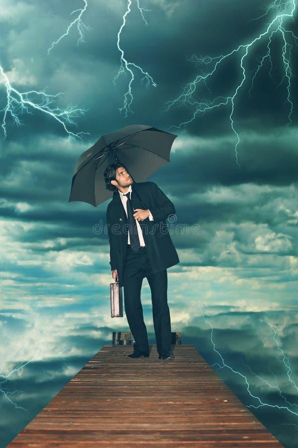 Homem de negócios com o guarda-chuva que enfrenta a tempestade foto de stock