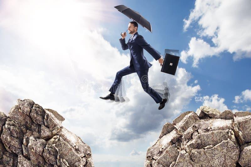 Homem de negócios com o guarda-chuva que salta em montanhas fotos de stock royalty free