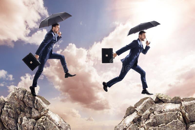 Homem de negócios com o guarda-chuva que salta em montanhas fotografia de stock