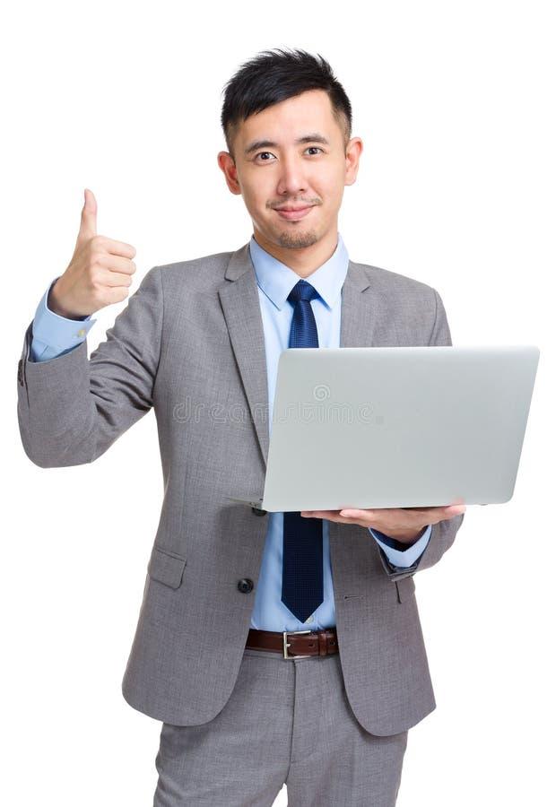 Homem de negócios com o portátil que mostra o polegar acima fotografia de stock