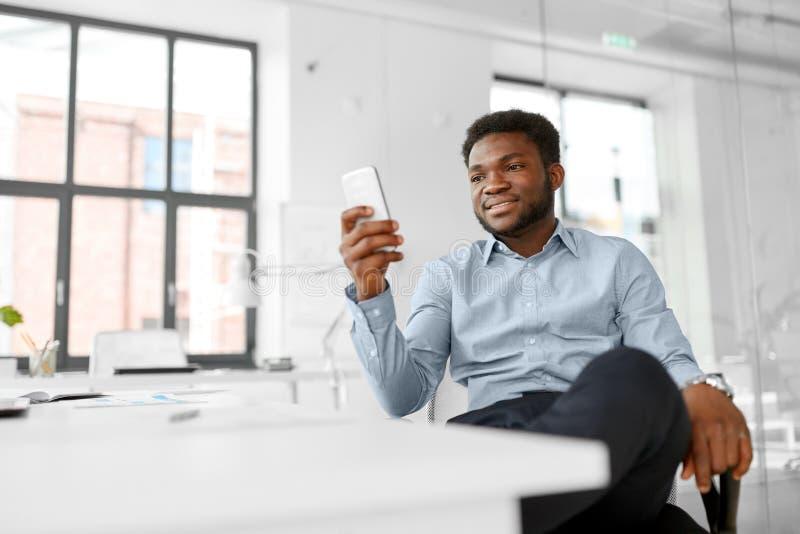 homem de negócios com o smartphone no escritório foto de stock royalty free