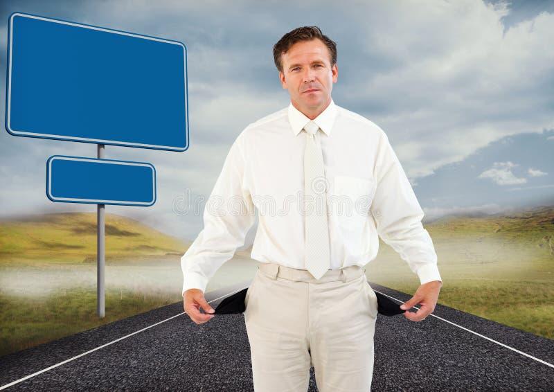 Homem de negócios com os bolsos vazios na estrada por sinais vazios imagens de stock