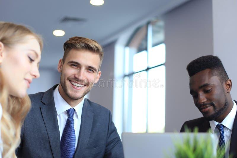 Homem de negócios com os colegas no fundo no escritório fotografia de stock