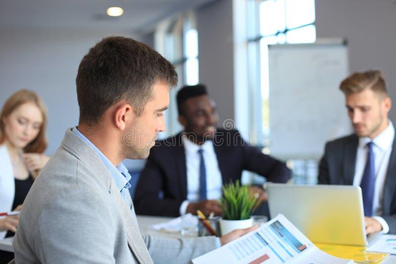 Homem de negócios com os colegas no fundo no escritório fotografia de stock royalty free