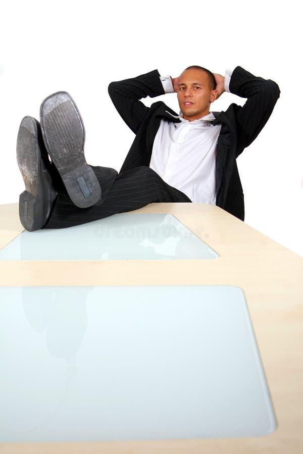 Homem de negócios com pés na tabela imagem de stock royalty free