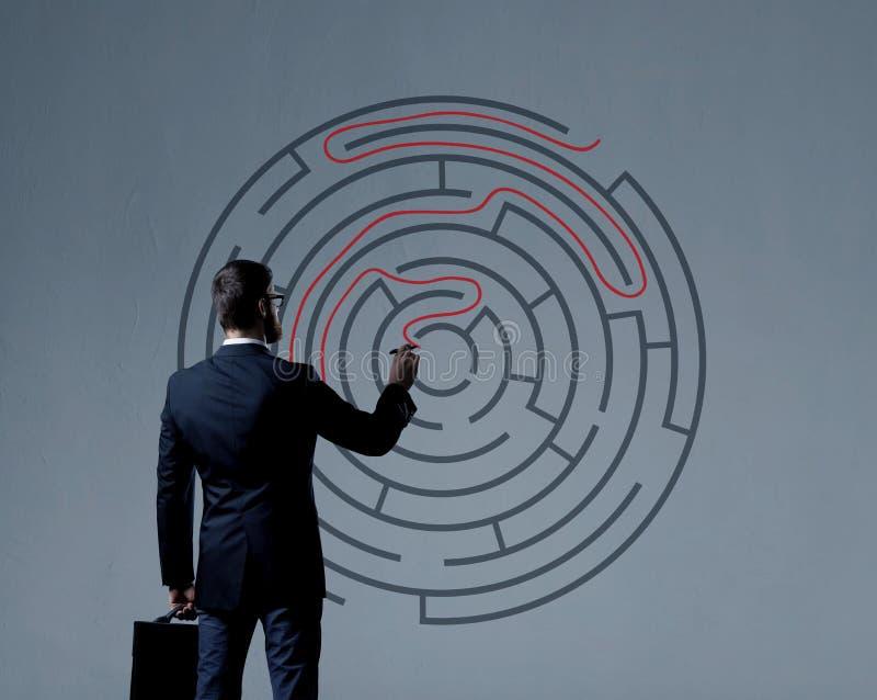 Homem de negócios com a pasta que está sobre o fundo do labirinto B imagens de stock royalty free