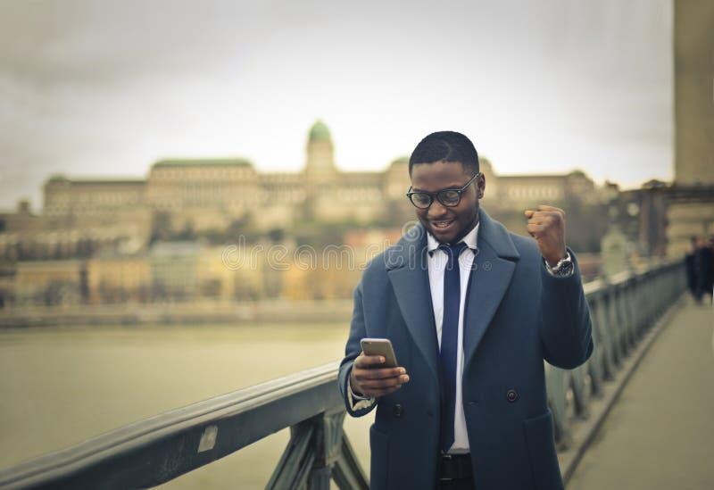 Homem de negócios com pose do telefone e do triunfo imagens de stock
