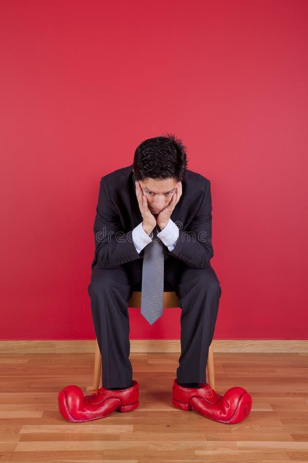 Homem de negócios com sapatas do palhaço foto de stock