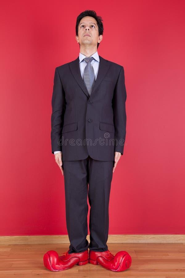 Homem de negócios com sapatas do palhaço imagens de stock royalty free