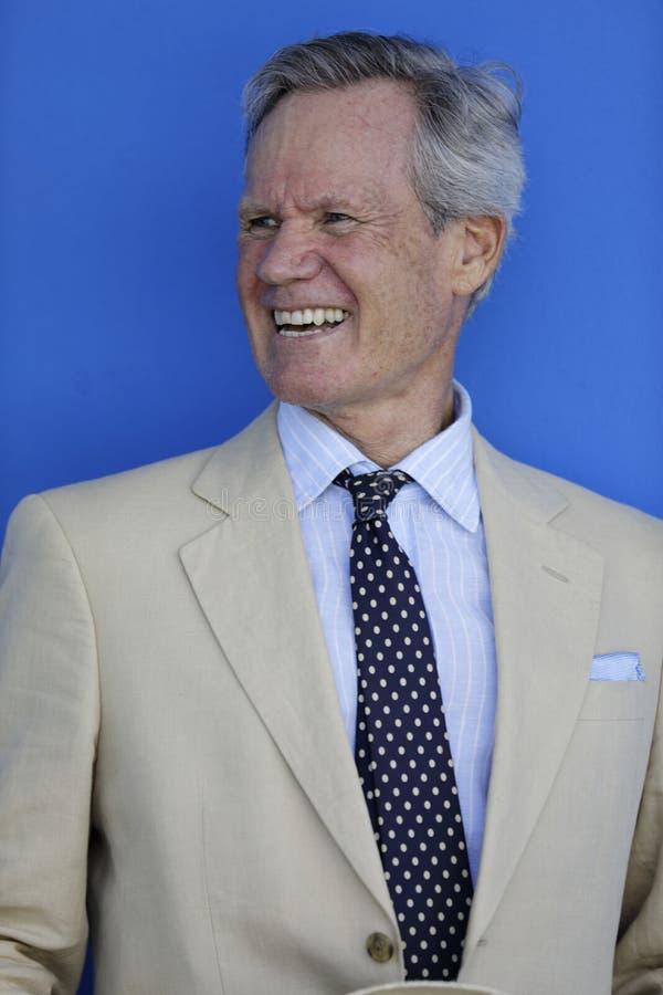 Homem de negócios com sorrir forçadamente grande que olha fora da câmera fotografia de stock royalty free