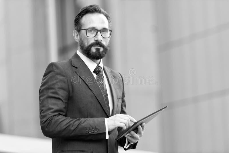 Homem de negócios com tabuleta à disposição no fundo do prédio de escritórios Homem de negócio que usa sua tabuleta fora do escri fotografia de stock royalty free