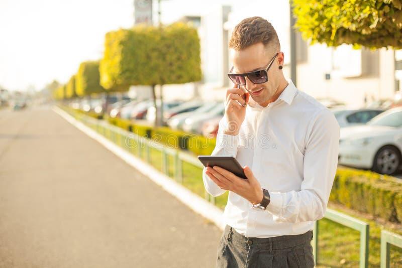 Homem de negócios com telefone celular e tabuleta nas mãos foto de stock