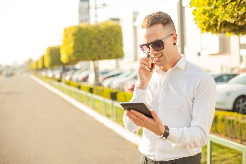Homem de negócios com telefone celular e tabuleta nas mãos fotografia de stock