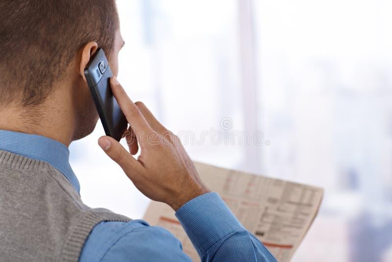 Homem de negócios com telefone e jornal fotografia de stock
