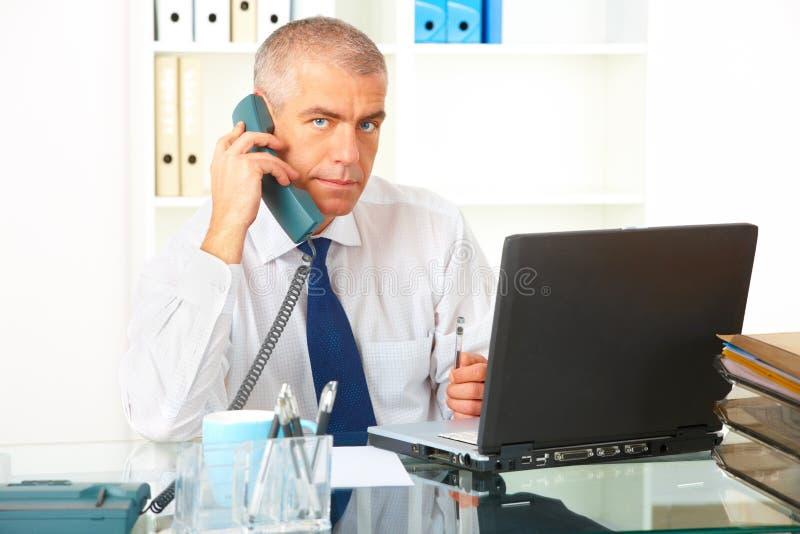 Homem de negócios com telefone e portátil fotografia de stock royalty free