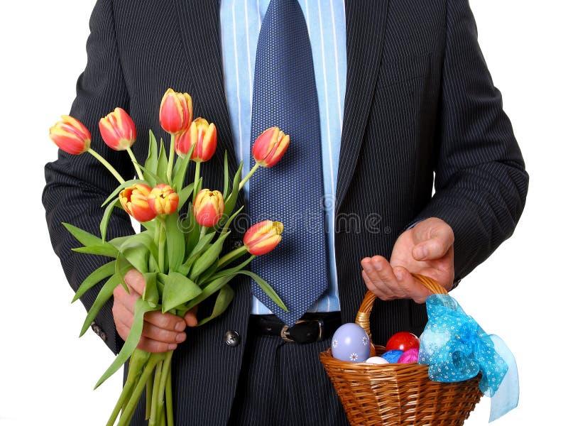 Homem de negócios com tulipas e cesta de vime completamente dos ovos da páscoa fotografia de stock