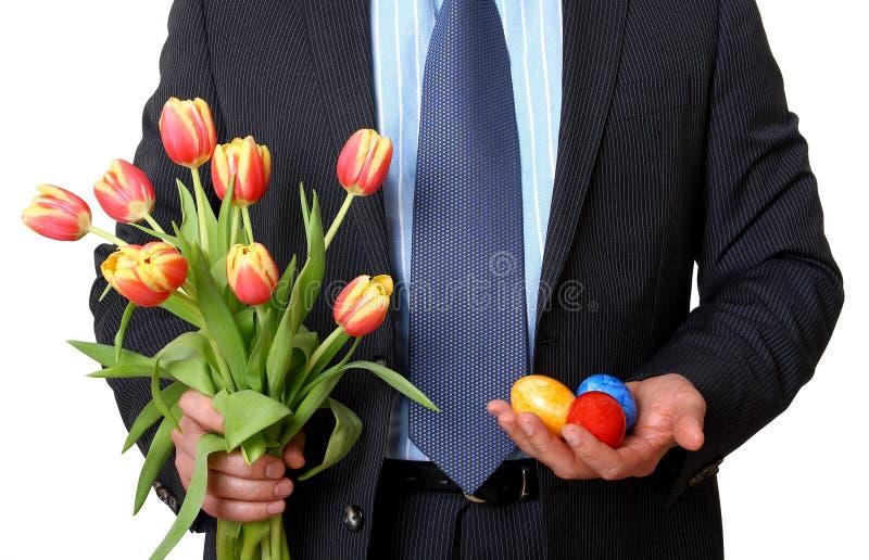 Homem de negócios com tulipas e três ovos da páscoa fotos de stock royalty free
