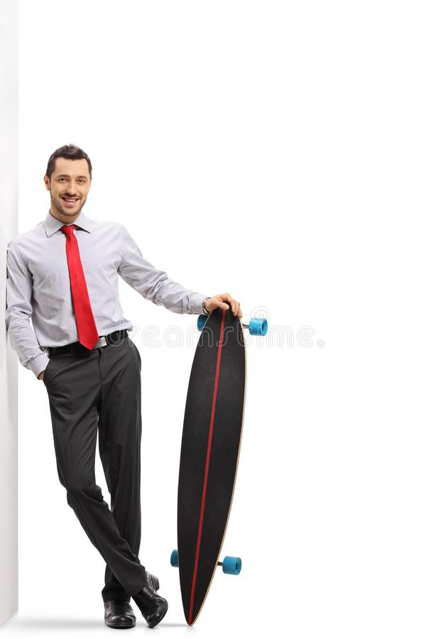 Homem de negócios com um longboard que inclina-se contra uma parede imagem de stock royalty free