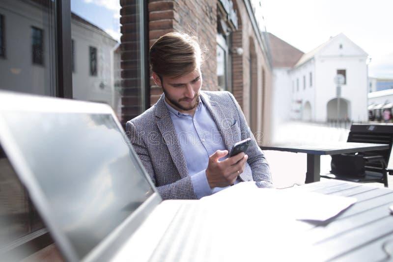 Homem de negócios com um smartphone que senta-se em uma tabela em um café da rua imagem de stock