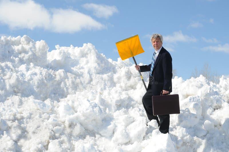Homem de negócios com uma pá e uma pasta da neve fotos de stock
