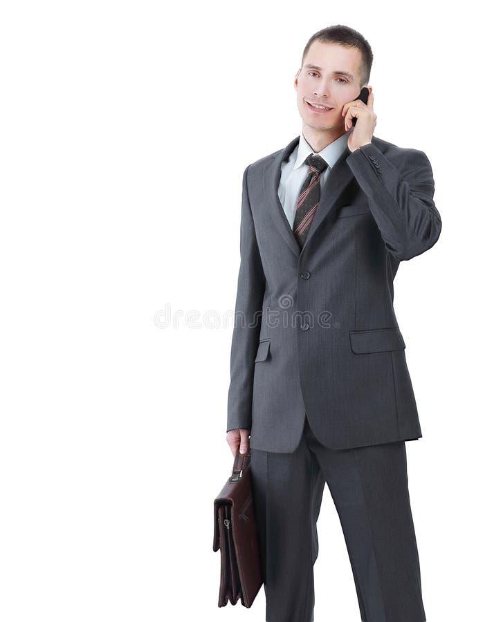 Homem de negócios com uma pasta de couro que fala em seu telefone celular imagens de stock