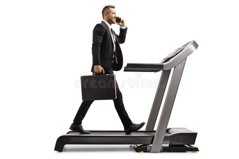 Homem de negócios com uma pasta que fala em um telefone celular e que anda em uma escada rolante foto de stock