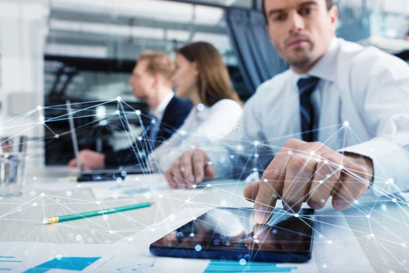 Homem de negócios com uma tabuleta que compartilhe de multimédios com a conexão a Internet foto de stock