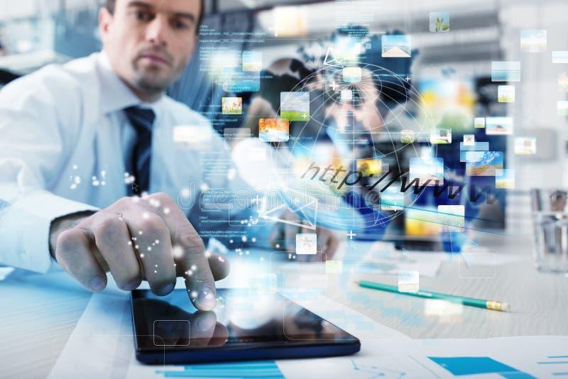 Homem de negócios com uma tabuleta que compartilhe de multimédios com a conexão a Internet fotografia de stock royalty free