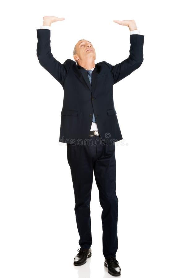 Homem de negócios completo do comprimento que empurra o teto invisível fotos de stock royalty free