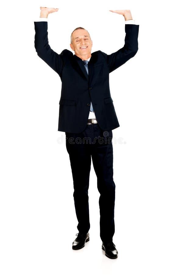 Homem de negócios completo do comprimento que empurra o teto invisível imagens de stock