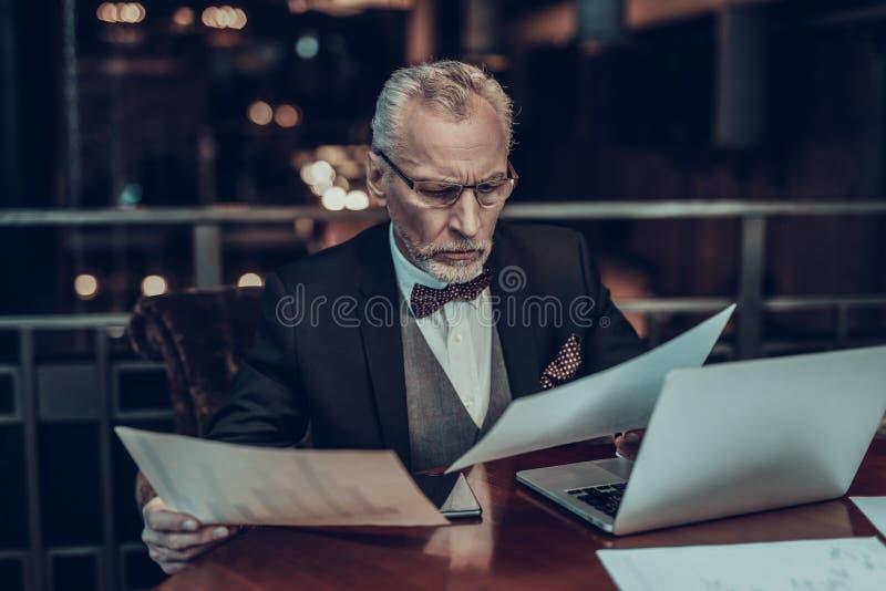 Homem de negócios concentrado velho que olha gráficos fotografia de stock