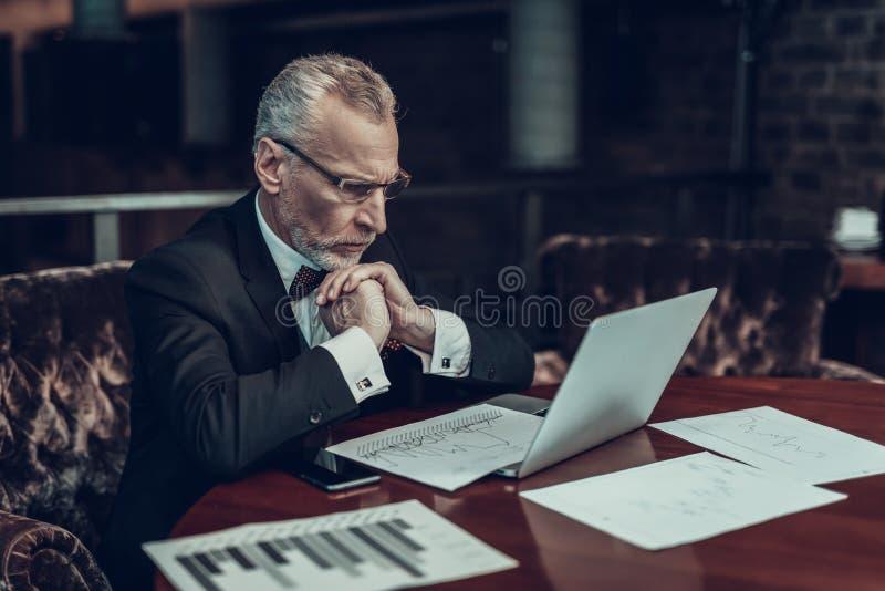 Homem de negócios concentrado velho que olha gráficos foto de stock royalty free
