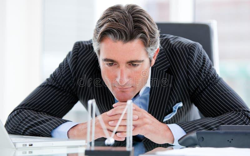 Homem de negócios confiável que olha esferas cinéticas imagens de stock