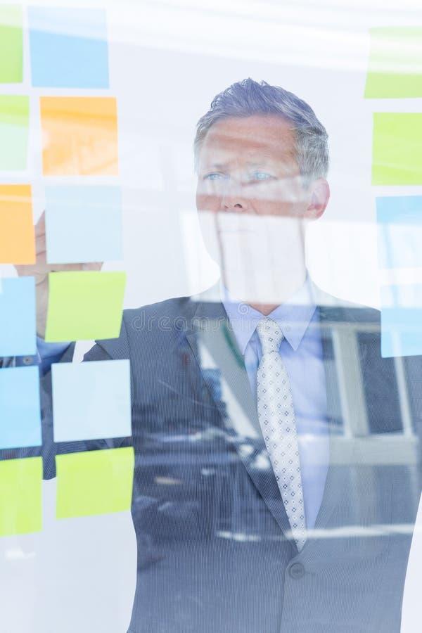 Homem de negócios confundido que olha post-it na parede imagens de stock royalty free