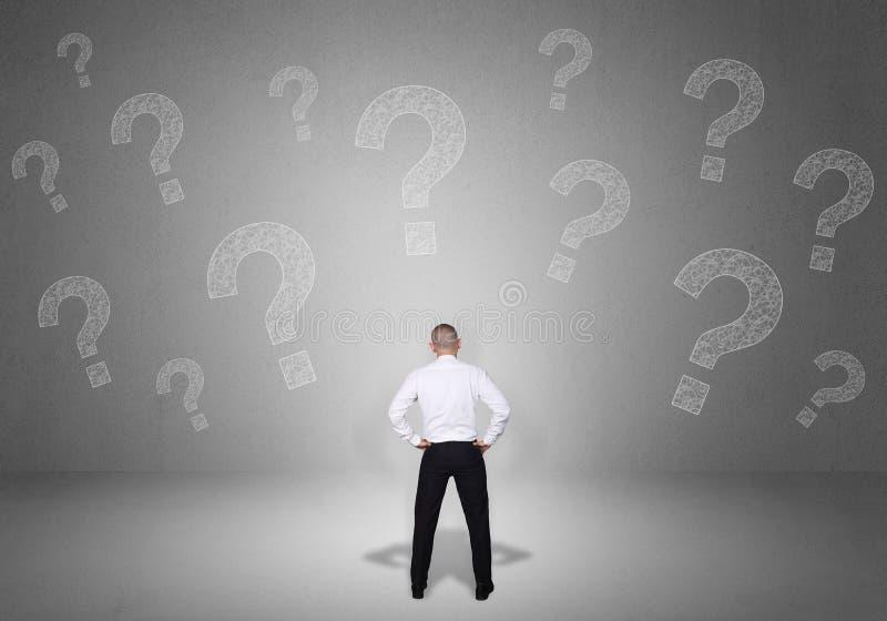 Homem de negócios confuso com pontos de interrogação fotografia de stock royalty free