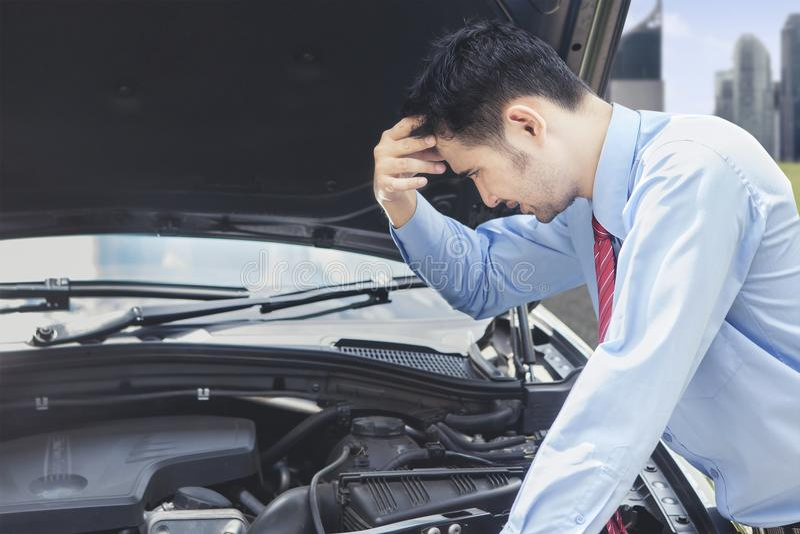 Homem de negócios confuso que olha o motor de automóveis fotos de stock